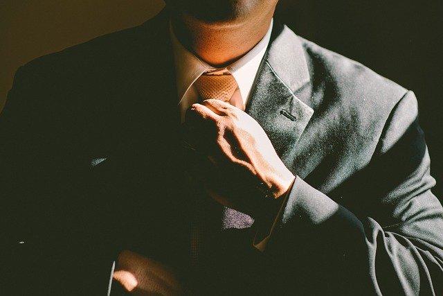 Business man adjusting his tie